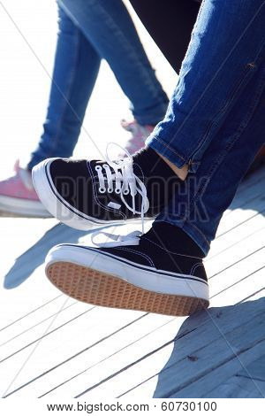 Legs Of Young Girl In Jeans And Sneakers