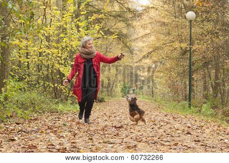 Middle Aged Lady Is Playing With Her Dog