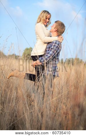 Young Adult Man Holding His Girlfriend Up