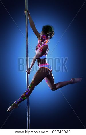 Sexy pole dancer posing with ultraviolet makeup
