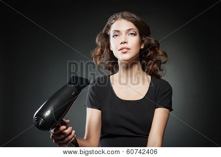 girl dries long hair by hairdryer over dark background
