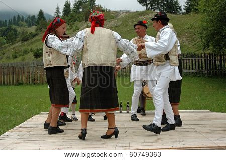 Villagers Dancing In Traditional Clothes