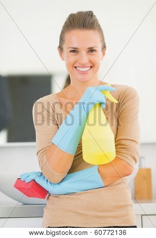 Portrait Of Smiling Young Housewife In Gloves With Spray Bottle In Bathroom