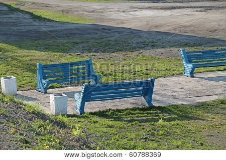 Three Blue Painted Benches Standing Next To Pathway At Sunny Day