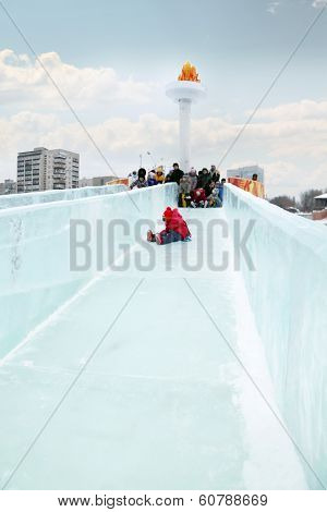 Little Girl In Red Rolls To Ice Slide In Ice Town In Perm, Russia, Created In Honor Of Winter Olympi