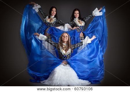 Trio of cute girls in traditional dance costumes