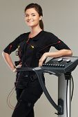 foto of stimulating  - Young woman in training costume near Electro Muscular Stimulation EMS machine - JPG