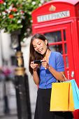 London woman on smart phone shopping texting on mobile phone holding shopping bags by red phone boot
