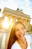 Happy laughing woman at Brandenburg Gate or Brandenburger Tor, Berlin, Germay. Lifestyle with smilin