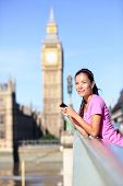 London woman runner listening to music on smartphone near Big Ben. Female running girl resting after