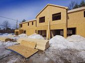 stock photo of 2x4  - Exterior framing of new town house construction in the suburbs - JPG