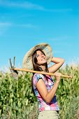 pic of hoe  - Successful female farmer carrying hoe in corn field - JPG