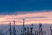 Fishing Boats Masts In Port With Sunset In Background.
