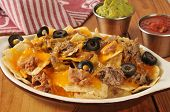 stock photo of nachos  - A dish of nachos with shreded beef beans cheddar cheese guacamole and salsa - JPG
