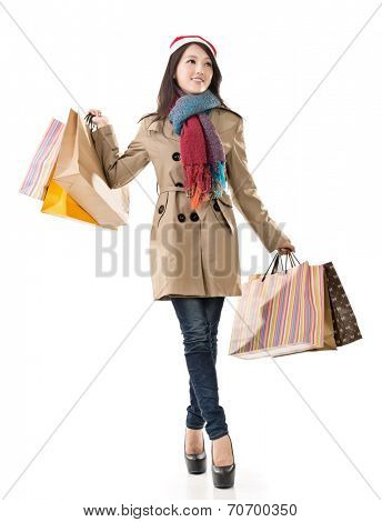 Happy shopping girl holding bags and gift box, wearing Christmas hat ,full length portrait isolated on white background.