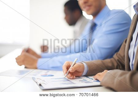 Young businesswoman working with spreadsheet with colleagues on background