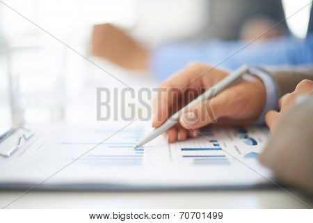 Hand of a young businesswoman working with spreadsheet