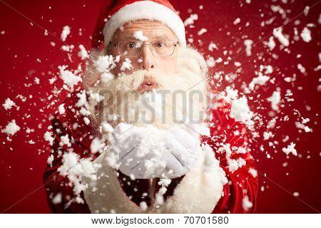 Santa Claus blowing snow and looking at camera