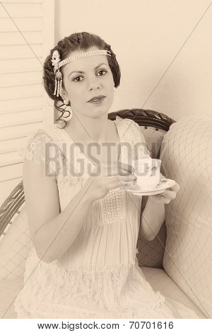 Attractive vintage 1920s woman sitting on a chaise longue