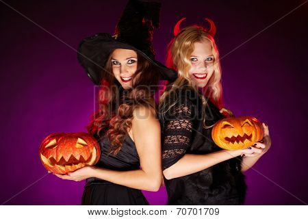 Portrait of two happy females with carved Halloween pumpkins