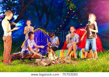 Happy Kids Around Bonfire In Summer Camp