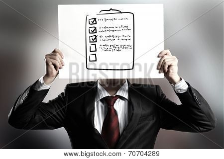 Businessman hiding his face behind paper sheet with sketches