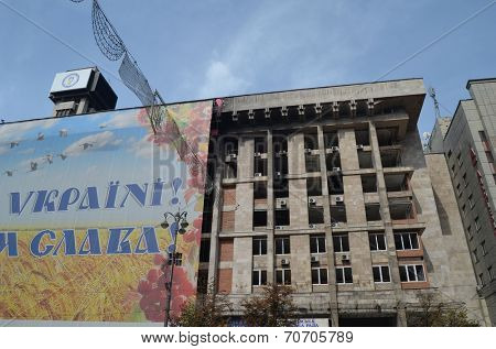 KIEV, UKRAINE -AUG 24, 2014: Downtown of Kiev.Burnt down the House of trade unions during riot in Kiev .Covered by huge poster - Glory to Ukraine for parade of victory.August 24 2014 Kiev, Ukraine