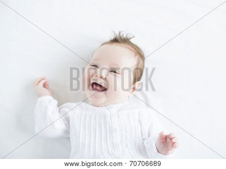 Adorable Baby Girl In A White Dress Laughing Toothless On A White Blanket