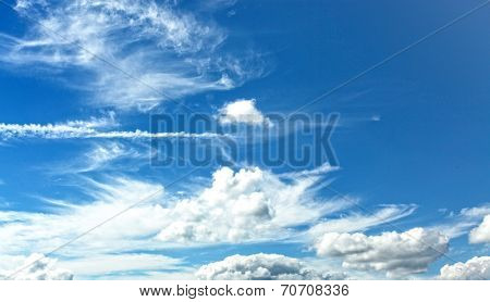 Abstract background of beautiful curly and sparse snowy white clouds like whitecaps over light bright blue sky in sunny spring clear day