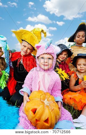 Boy holding Halloween pumpkin with his friends