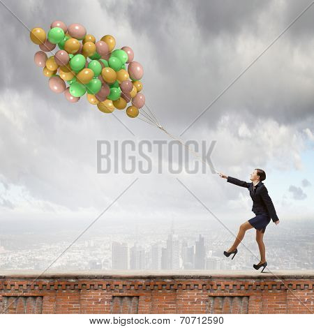 Young joyful businesswoman walking with bunch of colorful balloons