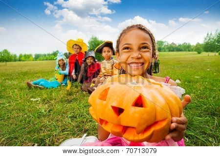 Happy African girl holds Halloween pumpkin