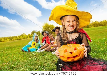 Wicked girl in witch dress with Halloween pumpkin