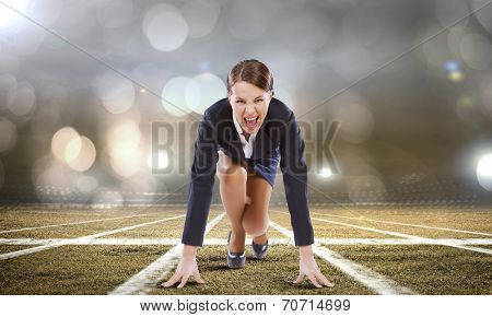 Young attractive businesswoman at stadium standing in start position