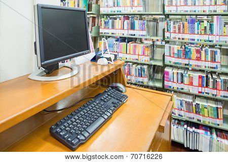 Computer In A Library With Many Books And Shelves In The Background