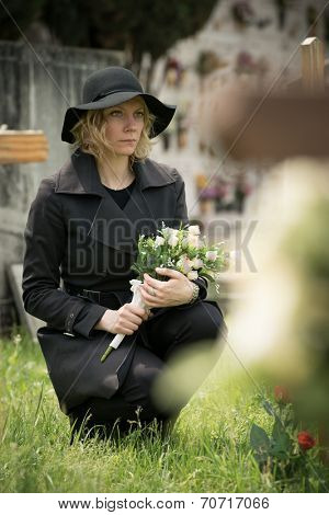 Woman at graveside with flowers