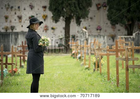 Woman standing at cemetery holding flowers