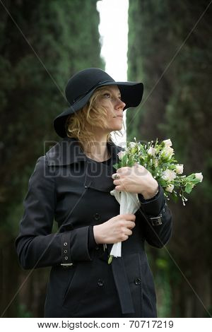 Close-up of a sad woman at cemetry holding flowers