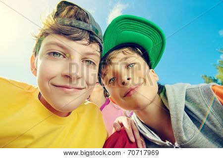 Two joyful boys looking at the camera against the blue sky. Summer.