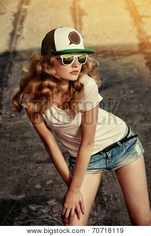 Beautiful modern girl posing outdoor. Youth style. Fashion shot.