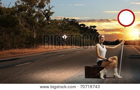 Young woman sitting on suitcase and holding roadsign