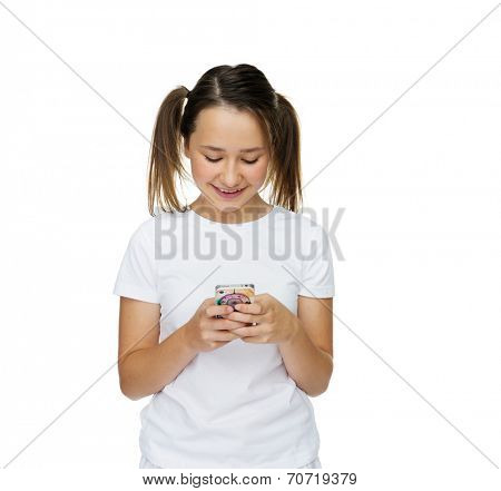 Young girl with her hair in pigtails standing reading a text message on her mobile phone smiling with pleasure at the news, on white