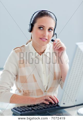 Pensive Businesswoman Working At A Computer With Headset On