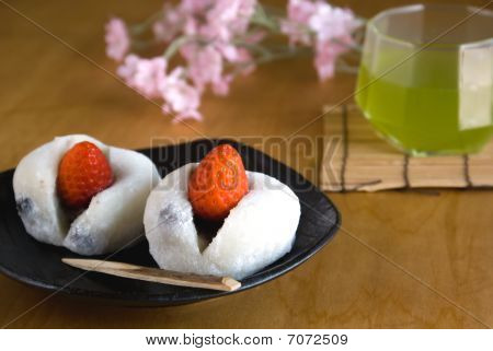 Two Japanese Sweets (ichigo Daifuku) With Green Tea And Flowers