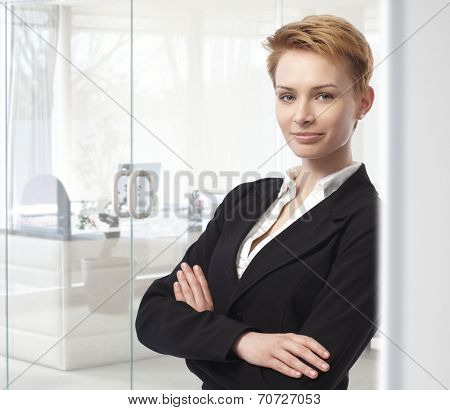 Young caucasian attractive businesswoman standing arms crossed at business office. Leaning against wall, looking at camera, smiling, confident, woman suit. Copyspace.
