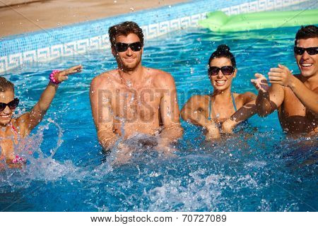 Young companionship splashing in outdoor swimming pool, having fun.