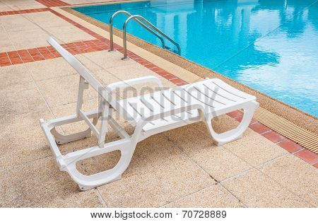 Relaxing Beach Chair Beside Grab Bars Ladder And Blue Swimming Pool