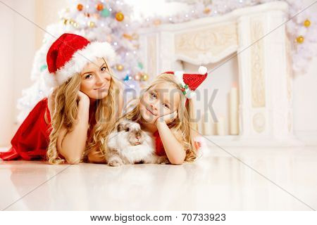 Mother and daughter dressed as Santa celebrate Christmas. Family at the Christmas tree. Woman and girl celebrate new year with bunny