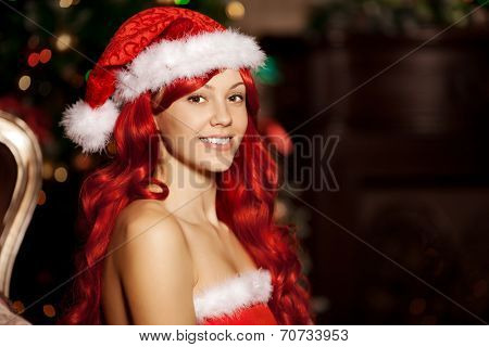 Young beautiful smiling santa woman near the Christmas tree. Fashionable luxury  girl celebrating New Year.
