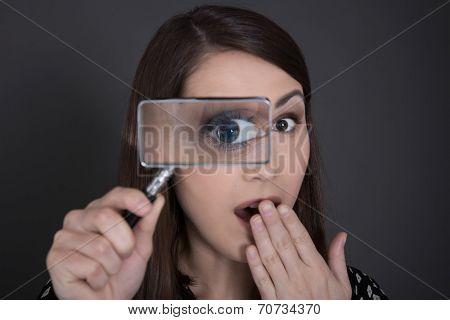 Nosy And Shocked Business Woman In Black Holding Magnifying Glass.